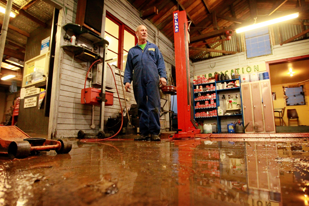 FLASH FLOOD: Dinsdale Roundabout Garage owner Peter Andersen surveys the damage after a burst water main flooded his shop floor.