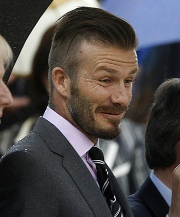 English football identity David Beckham reacts during the Olympic torch handover ceremony in Athens.