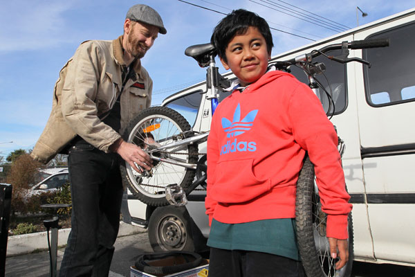 Bike mecahnic Jono Kitt fixes Tyrese Emery's bicycle during a free bicycle maintenence workshop run by volunteers from ICECycles (Inner City East Cycles) outside the Delta Centre.