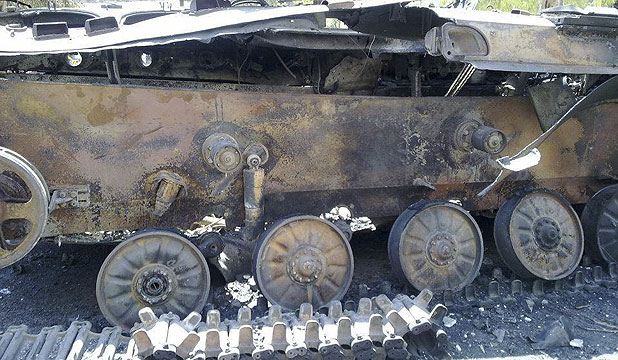 CARNAGE OF WAR: A damaged tank is seen in the Damascus suburb of Erbeen.