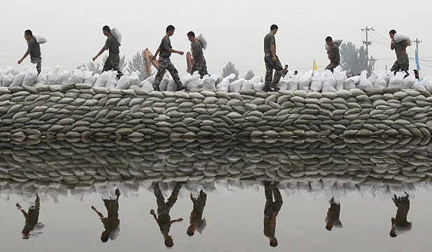 MORE TO COME: Chinese People's Liberation Army soldiers place sandbags to block a breaching dyke after heavy rainfalls hit the Fangshan district of Beijing.