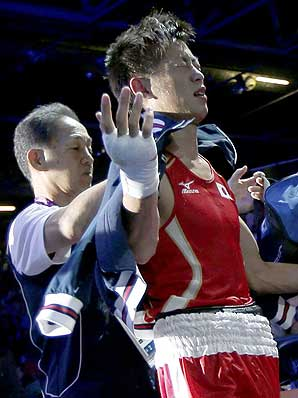 A distraught Satoshi Shimizu of Japan walks from the ring after losing to Azerbaijan's Magomed Abdulhamidov in their men's bantam (56kg) boxing match at the London Oly
