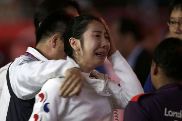 South Korea's Shin A Lam reacts as she is escorted following a sit in after being defeated during the women's epee individual semifinal fencing competition at the London 2012 Olympic Games.