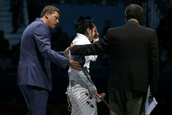 South Korea's Shin A Lam reacts as she is escorted after being defeated by Germany's Britta Heidemann during their women's epee individual semifinal fencing competition at the London 2012 Olympic Games.