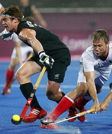 New Zealand's Andrew Hayward (left) challenges Germany's Moritz Fuerste during their men's group B hockey match at the London 2012 Olympic Games which ended