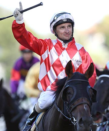 Jockey Opie Bosson waves to the crowd on his way back to the birdcage aboard The Party Stand after winning the Group One New Zealand Stakes at Ellerslie.