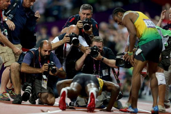 Jamaica's Usain Bolt performs for photographers after winning the men's 200m final at the London Olympics to complete back-to-back sprint doubles.