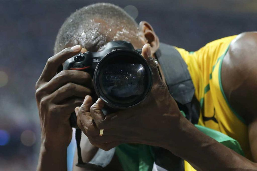 Jamaica's Usain Bolt takes pictures with a photographer's camera as he c
