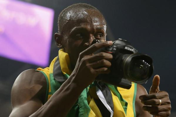 Jamaica's Usain Bolt takes pictures with a