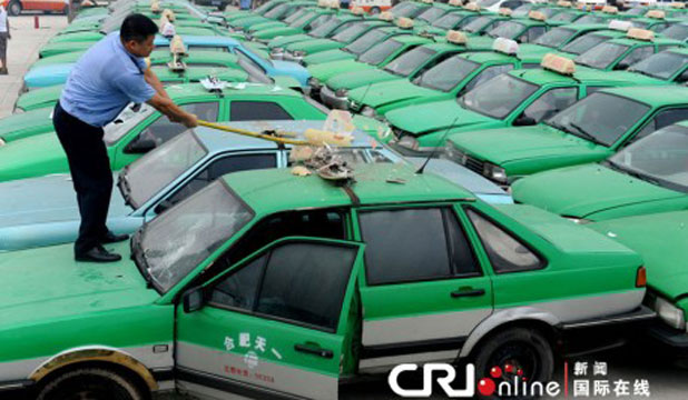 A Chinese worker begins demolition of one of 156 illegal taxis seized in the city of