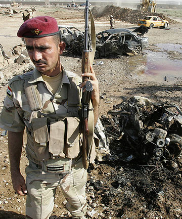BATTLE AGAINST MILITANTS: Security personnel inspect the site of a bomb attack in Kirkuk.