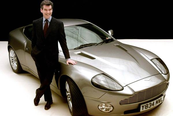 James Bond actor Pierce Brosnan poses for photographers with the Aston Martin V12 Vanquish for the filming of Die Another Day.