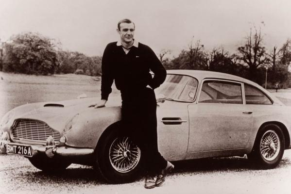 James Bond (Sean Connery) leans on the Aston Martin DB5 from Goldfinger.