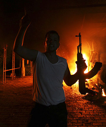 PROTEST BECOMES ASSAULT: An armed protester outside the burning US Consulate in Benghazi, Libya.