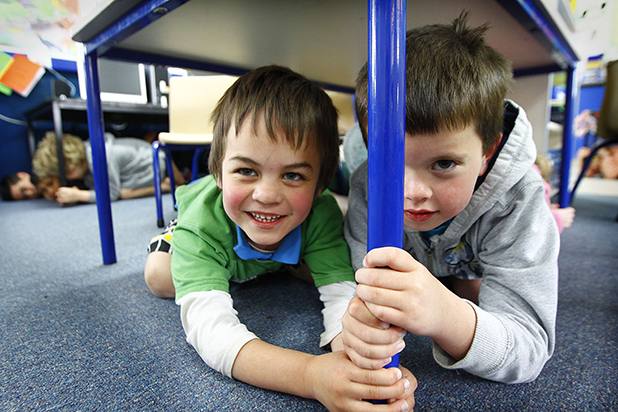 BE PREPARED: Te Rapa Primary School pupils Tangaroa McLean, left, and Harry Bishop prepare to drop, cover and hold for today's nationwide earthquake drill.