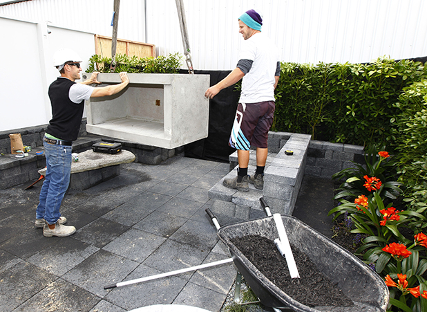SETTING UP: Richard Boobyer, right, gets help from Nathan Badger in placing an outdoor fireplace
