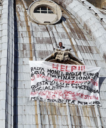 Marcello Di Finizio, a 49-year-old man from Trieste, northern Italy, stands on the dome of Saint Peter's Basilica holding a banner reading,