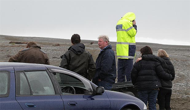 SEARCH: Family an friends wait with police officer Mike Jackson near the Rakaia River mouth where a whitebaiter went missing last evening.