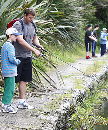 GONE FISHING: Edventure teacher Mark Bridger shows the boys how to catch a trout at Hamilton Gardens.