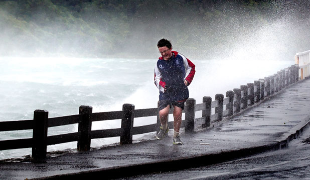 A lone runner finds the going tough as he struggles against headwinds and sea spray at Evans Bay on Saturday.