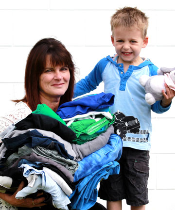 Care, Share and Wear founder Linda Cook and her nephew Jake Hill, 3, with a bundle of clothes donated for Taranaki children.