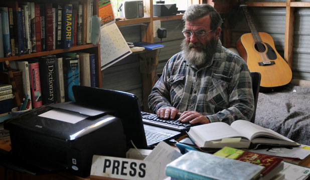 Tom O'Connor at work on his latest book in his ''man cave'', behind a Press sign he souvenired from the last meeting of the defunct Picton Borough Council.