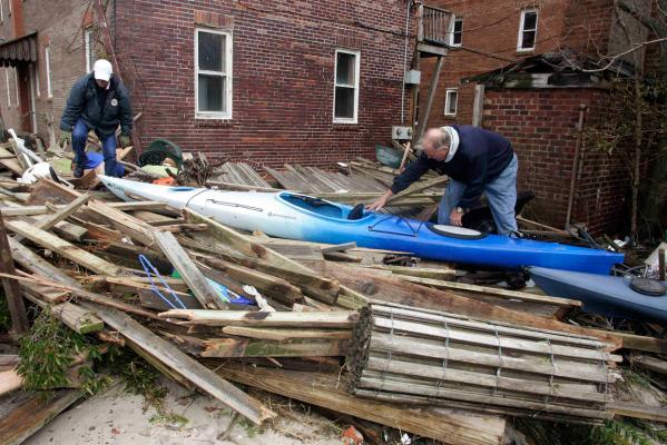 Residents walk along Broadway Avenue as they inspect damage from Hurricane Sandy in Point Pleasant Beach, New Jersey.