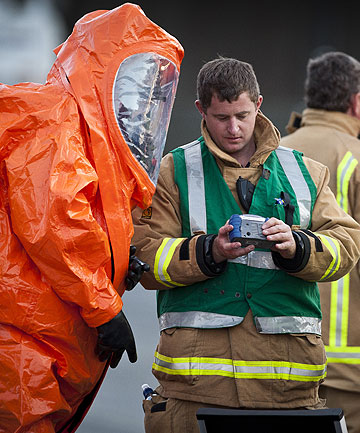 SUITED UP: Fire Service staff were on site in protective sealed suits to control the leak.