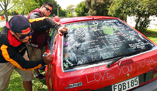 FRIENDS PAY TRIBUTE: Joshua Tanuvasa's close friends, Paeturi Maletino, left, and Chad Salvatierra, write tributes to the popular teen on the car they used to travel in together.