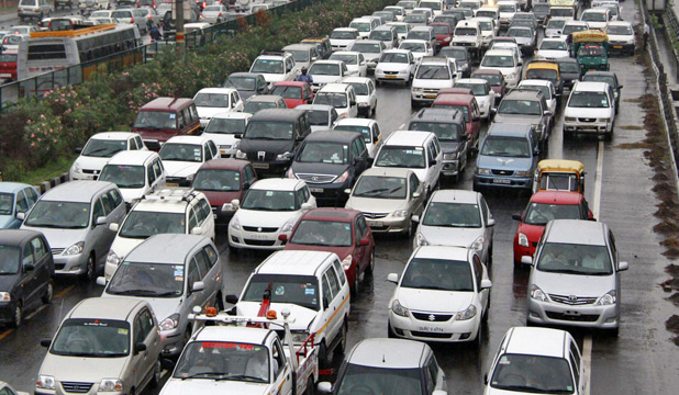 Heavy traffic moves along a busy New Delhi Rd.