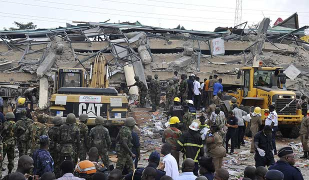 Rescue workers look for survivors from the debris of a collapsed four-storey building in Accra