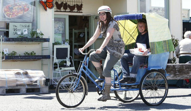 Geraldine Stones pedals the  rickshaw bike at Mapua with Mapua Trading Co owner Heather Cole