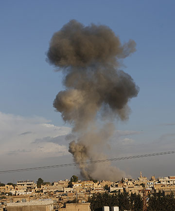 BOMBING RUN: Smoke rises over the Syrian town of Ras al-Ain after an air strike, seen from the Turkish border town of Ceylanpinar.