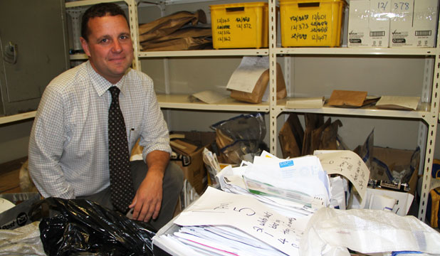 Detective Grant Miller with some of the thousands of undelivered mail items found at the Frankton Rd address of a NZ Post staffer