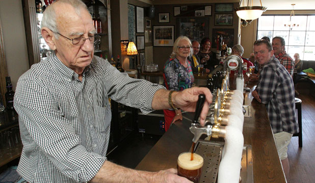 Stan O'Keefe, of Bailies Bar & Restaurant, pours a beer for the first customers at their newly opened Edgeware Village location, with wife Lynne behind the bar in the background.