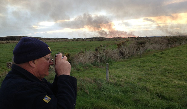BLAZE ON THE HORIZON: Warren Owen takes pictures of the fire which is believed