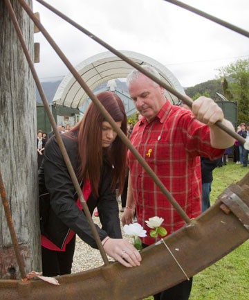 Malcolm Campbell Sr and his daughter Kerry place a flower during a public service at Blackball Workers' Museum in memory of Malcolm Campbell, who died in the Pike River mine.