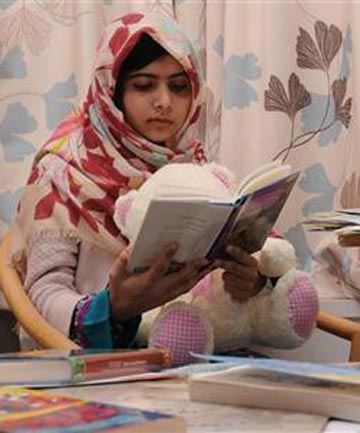Pakistani schoolgirl Malala Yousufzai reads a book as sh
