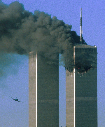 Hijacked United Airlines Flight 175 (left) flies toward the World Trade Center twin towers shortly before slamming into the south tower as the north tower burns following an earlier attack by a hijacked