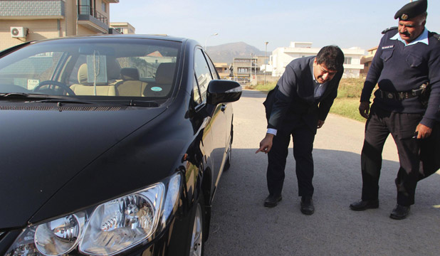 Senior journalist for the Geo News television station Hamid Mir points to his car where a bomb was found underneath,
