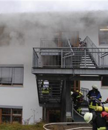 Firemen attend the scene of a fire at a workshop for disabled people in Titisee-Neustadt in the Black Forest region in south west Germany.