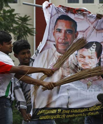 Muslim protesters hit caricatures of US President Barack Obama and Florida pastor Terry Jones with brooms during a protest, against a US-made film they consider blasphemous to Islam, near US consulate-general, in the southern Indian city