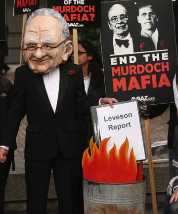 A protest group campaigning against the political dominance of Rupert Murdoch stage a mock burning of a copy of the Leveson Report outside the Queen Elizabeth II centre.