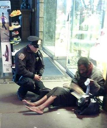 New York City Police Officer Larry DePrimo presents a barefoot homeless man in New York's Time Square with boots.