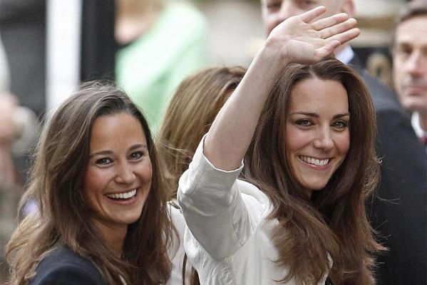 Kate Middleton waves as she arrives with her sister Pippa at The Goring hotel in London.