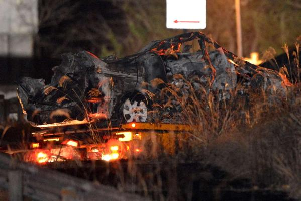 The burnt wreckage of a minivan, which was crushed and caught fire in Sunday's accident, is moved on a transporter out of the Sasago