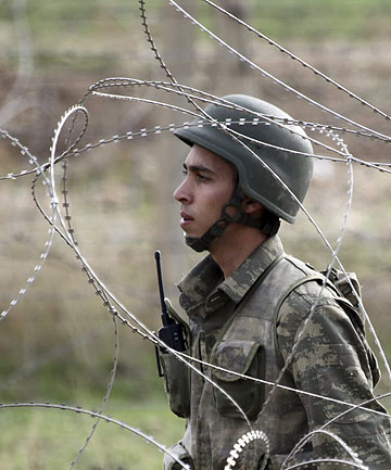 ON ALERT: A Turkish soldier on the border takes up a position as gunfire is heard in the northern Syrian town of Ras al-Ain.