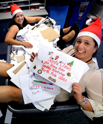 Postal elves Casey Warbrick, left, and Ingrid Ropeti hold Santa letters received at NZ Post.