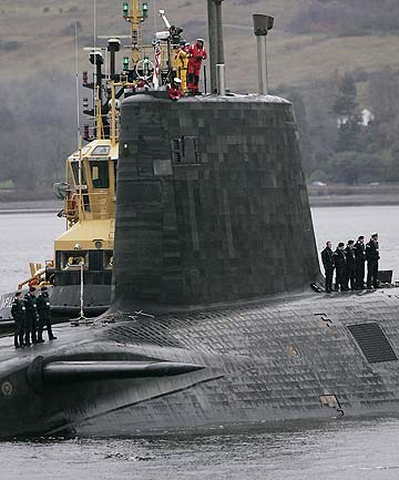 Crew from HMS Vengeance, a British Royal Navy submarine, look out from the conning tower as they return along the Clyde river to the Faslane naval base near Glasgow