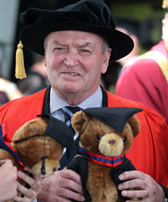 Sir Graham Henry poses for a photo with graduation teddies.